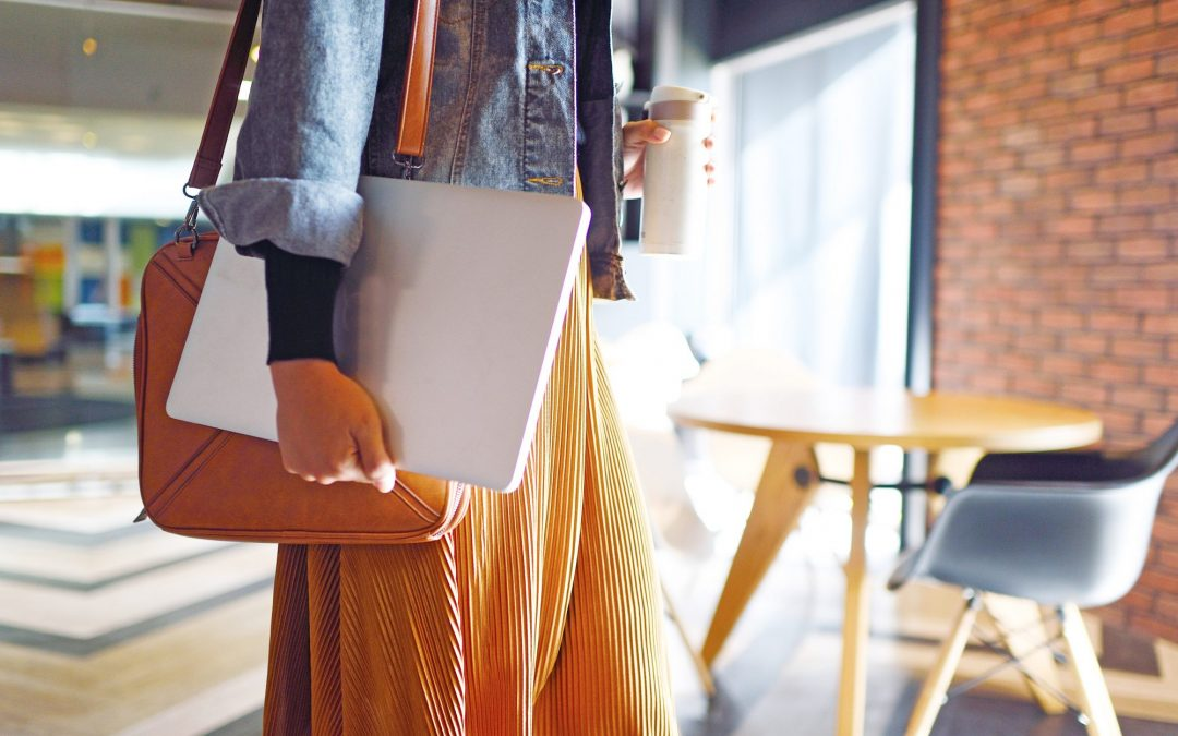 A image of a woman with a briefcase and laptop on her way to work.